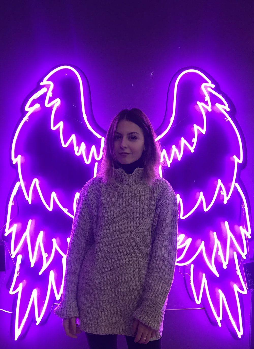 woman standing in front of purple wings neon light