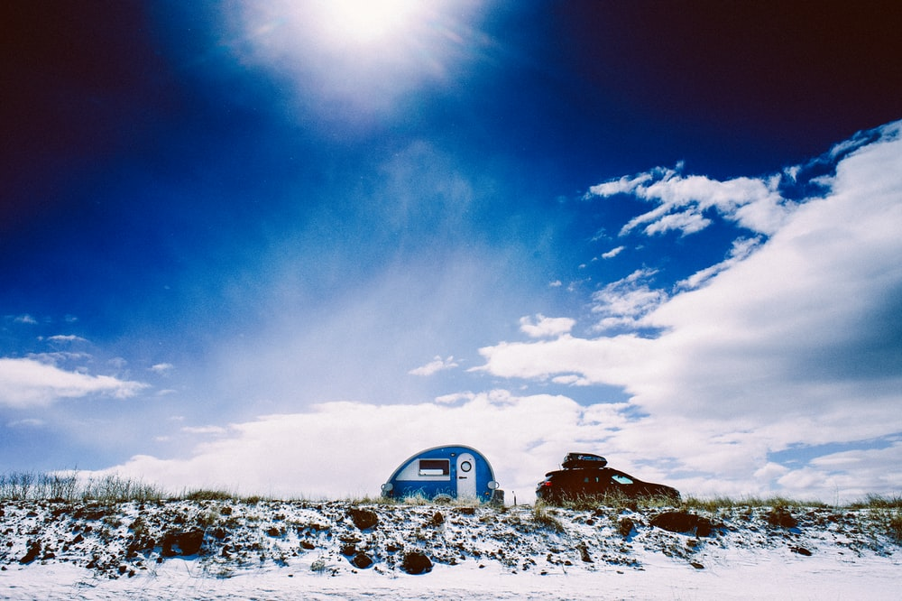 white and blue trailer under blue calm sky