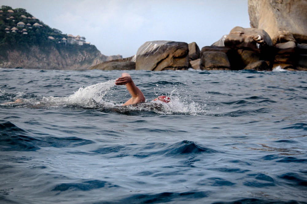 person swimming across brown rocks