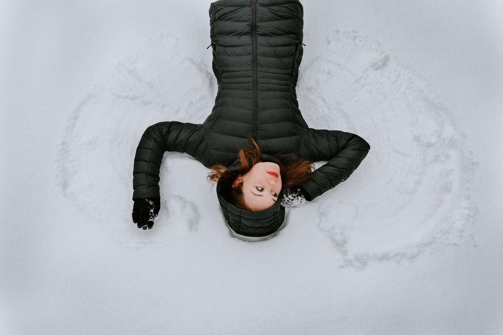 woman wearing black jacket lying on snow