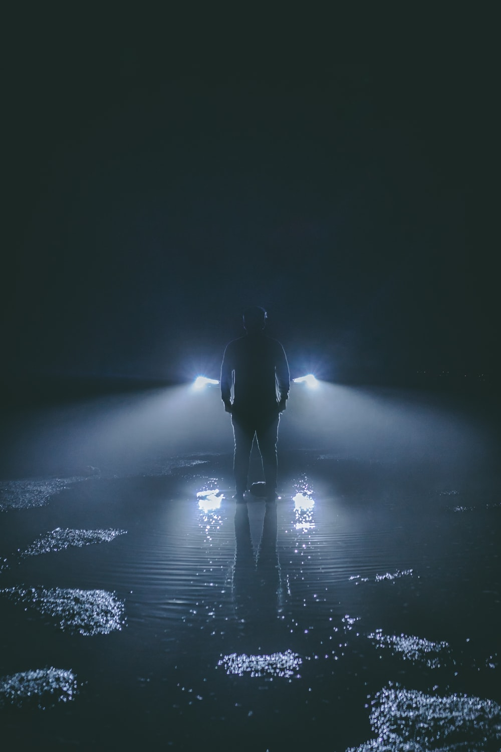 silhouette of person standing near car