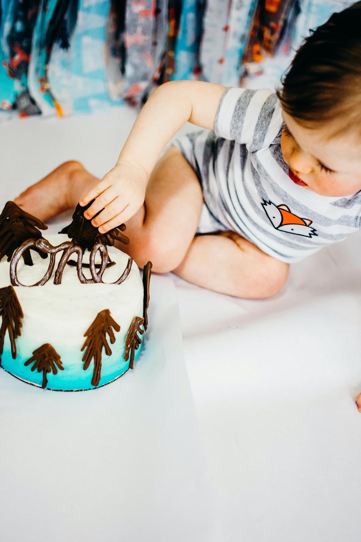 boy lying on floor near cake