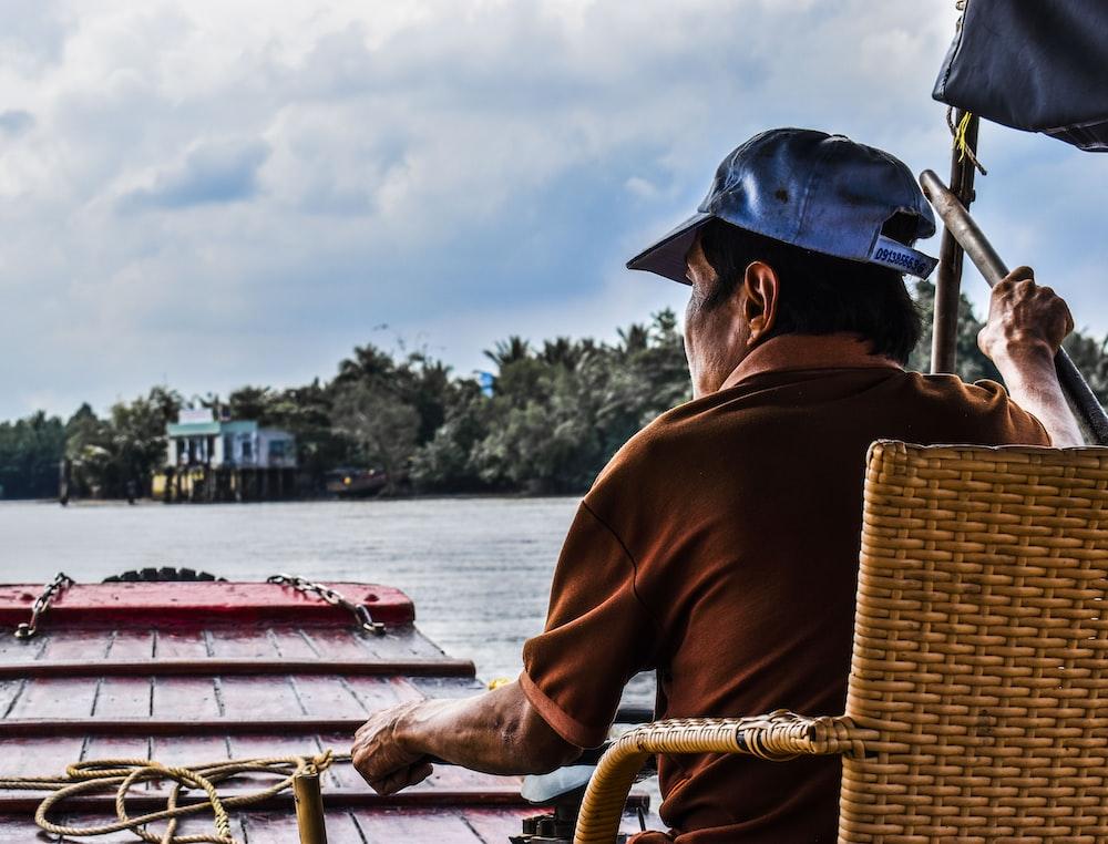 man sitting on wicker chair on boat