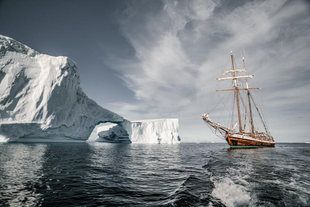 brown boat near glacier during daytime