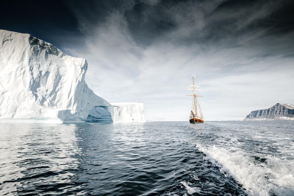 brown wooden sail ship sailing at sea near iceberg