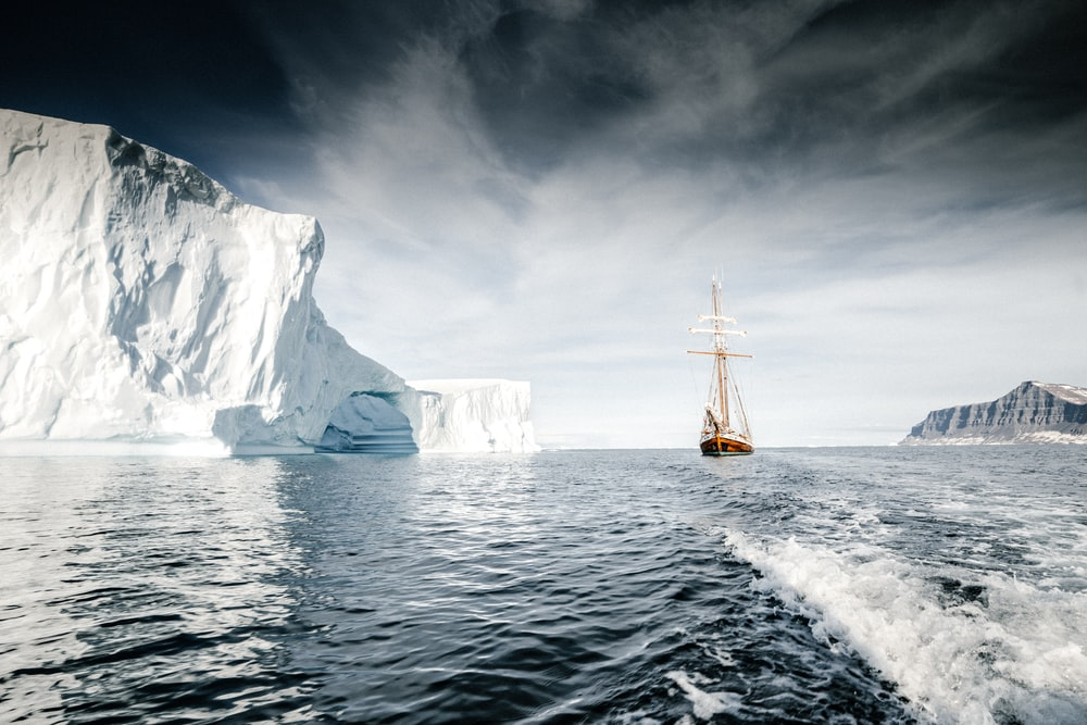 brown wooden sail ship sailing at sea near iceberg