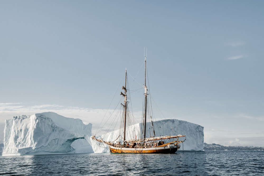 brown boat near ice berg during daytime
