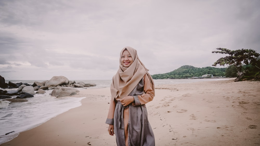 smiling woman wearing hija standing on seashore