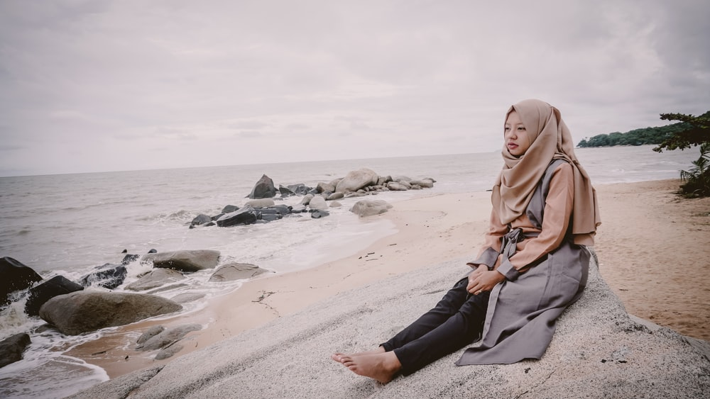 woman wearing hijab scarf and black pants sitting on shore