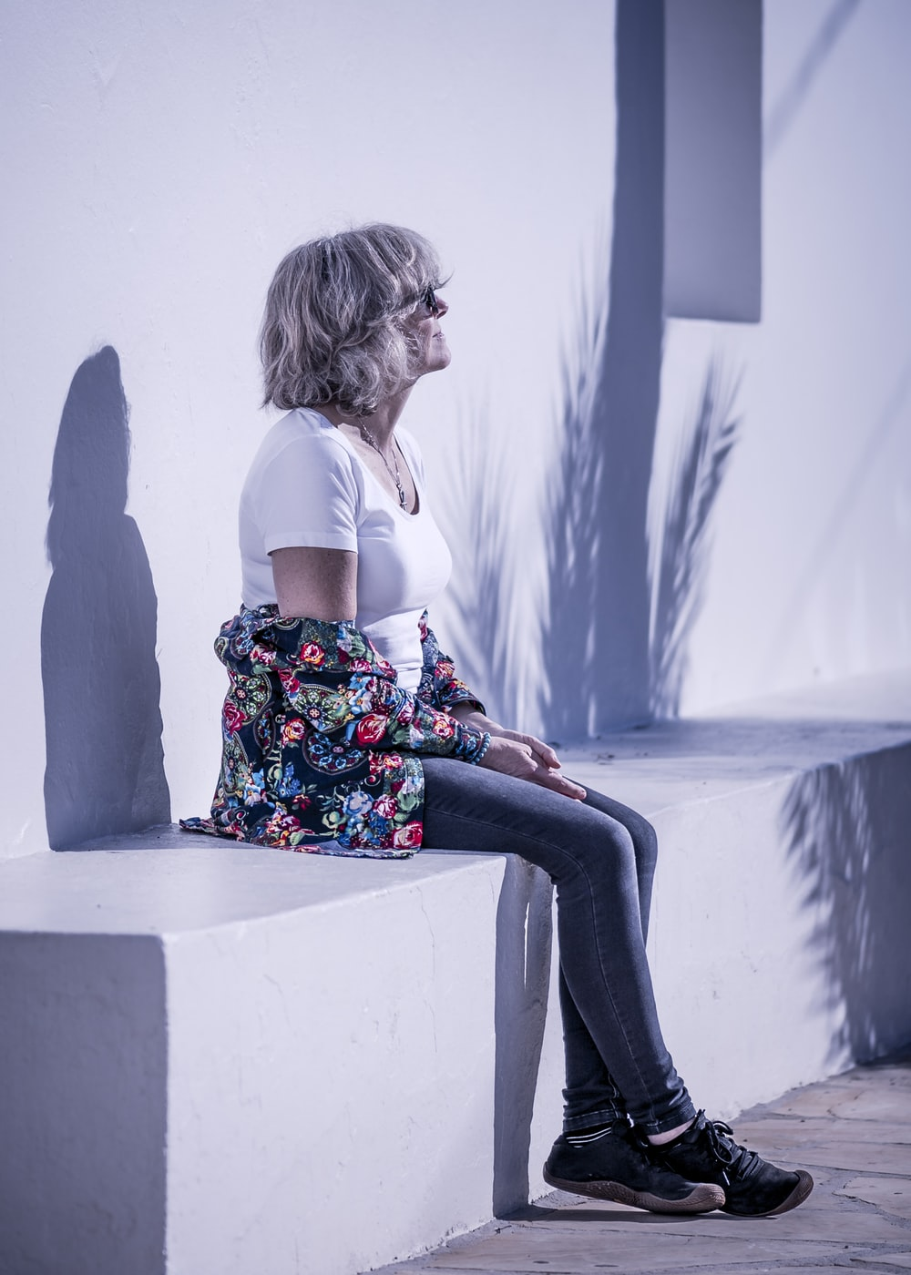 woman in white shirt and skinny jeans sitting on concrete seat