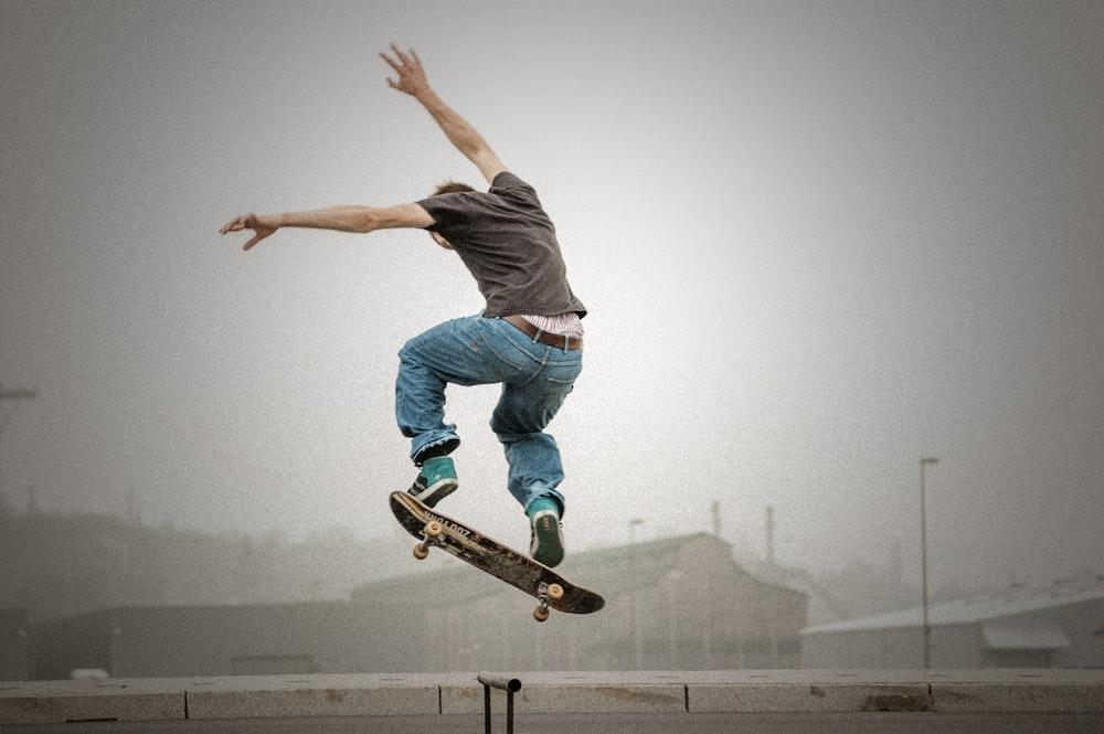 man wearing grey shirt doing skateboard tricks on air