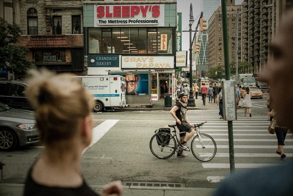 person riding bicycle stop of pedestrian lane during daytime