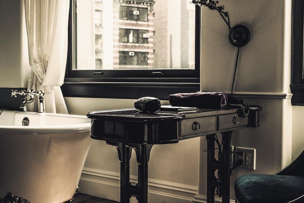 black wooden table near bathtub and wibdow