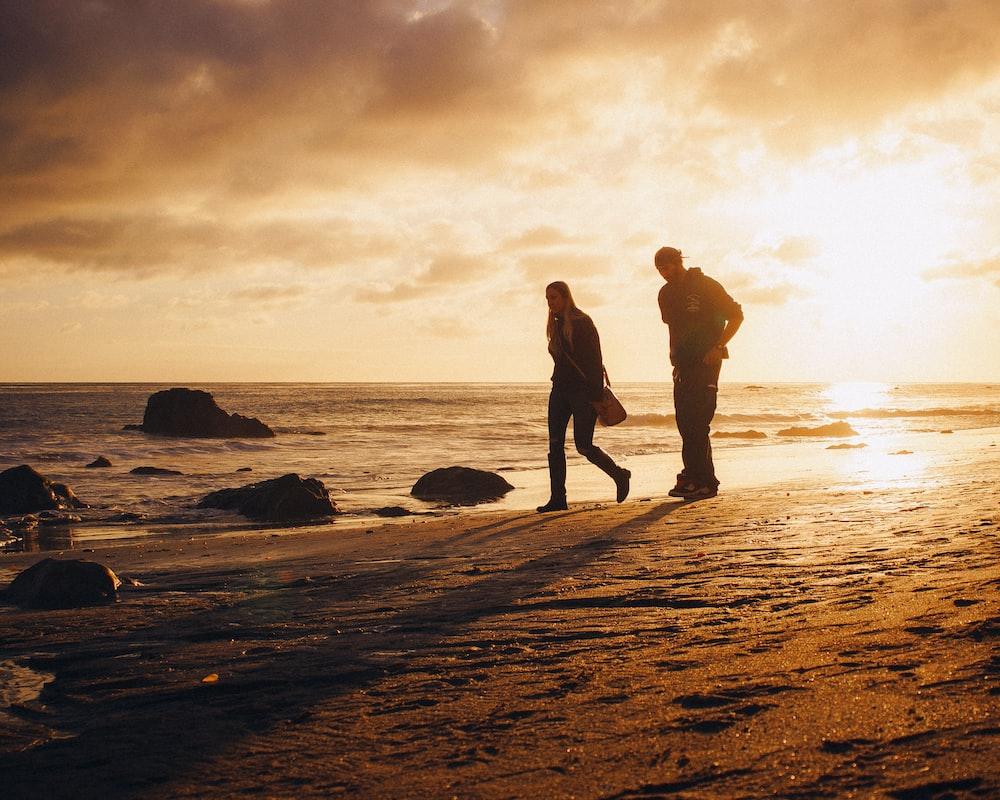 man and woman walking on seashore during sunset