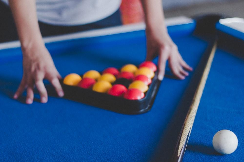 man preparing balls on pool table
