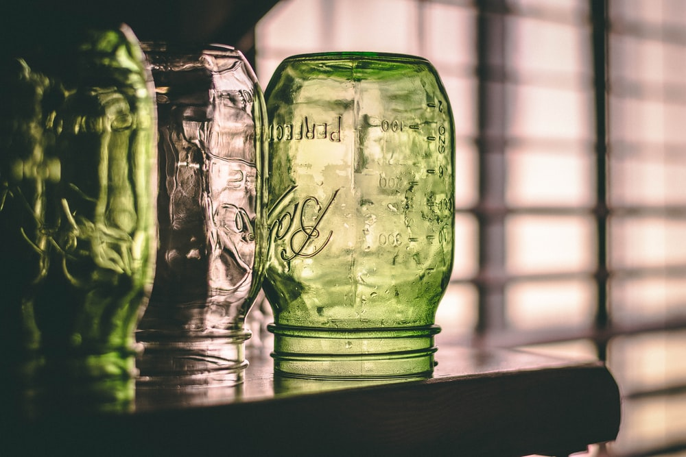 several assorted-color glass Ball Mason jars placed upside down