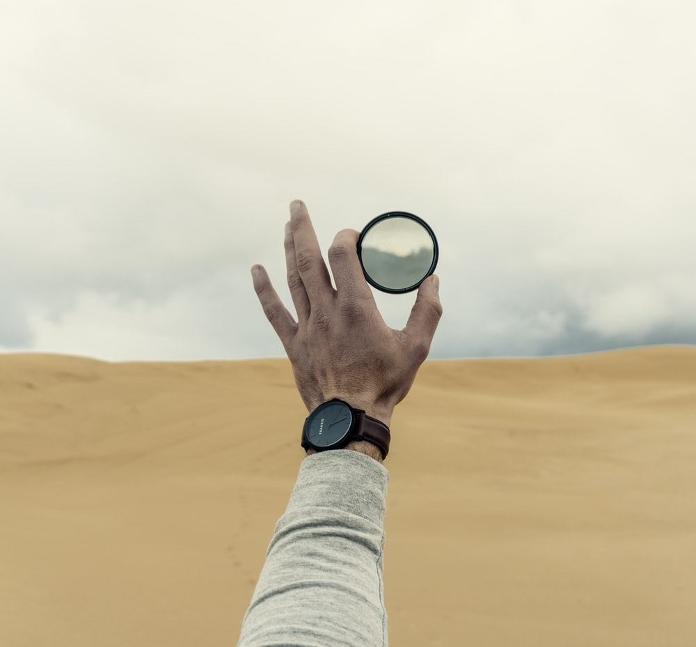 person holding lens during daytime