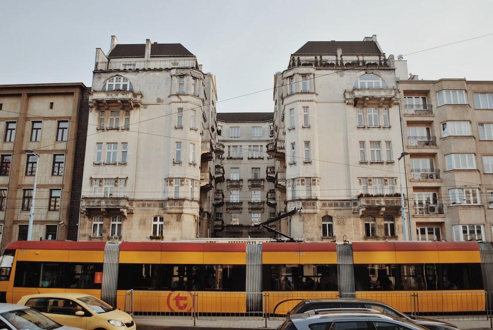 yellow bus near high rise building