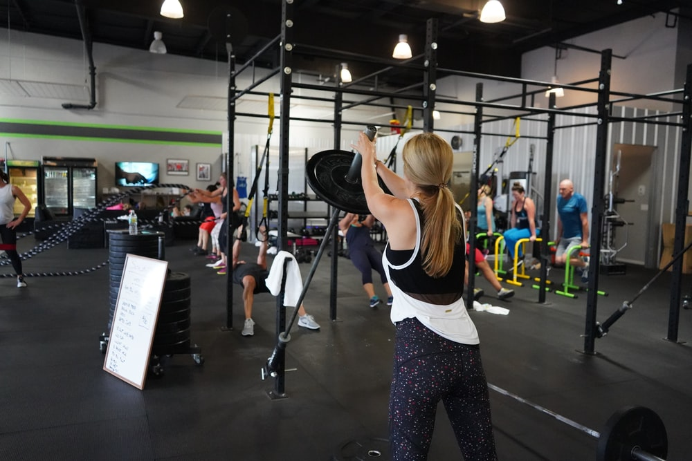 people doing exercise inside gym