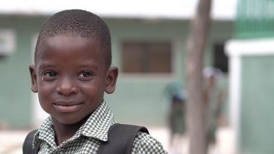 selective focus photography of boy wearing white collared shirt haiti zoom background
