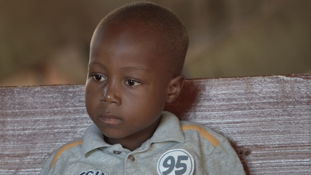 boy wearing gray button-up collared shirt