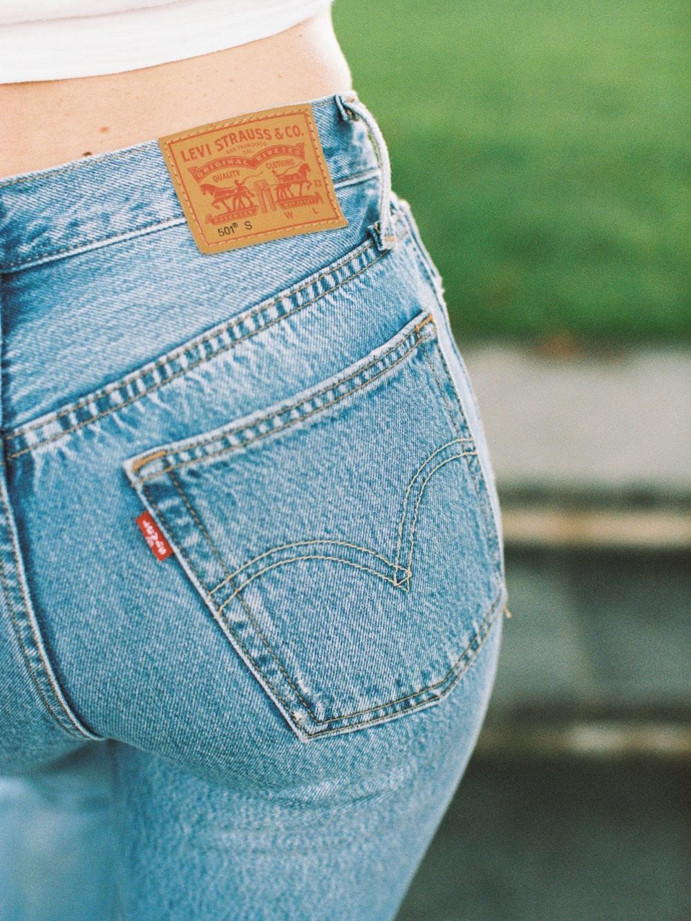 shallow focus photo of person wearing blue Levi denim bottoms