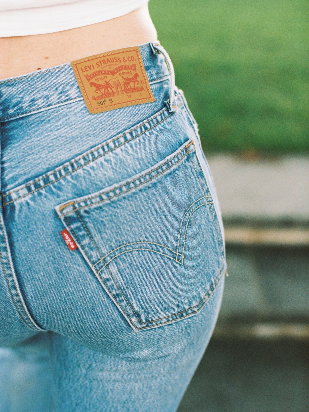 shallow focus photo of person wearing blue Levi denim bottoms