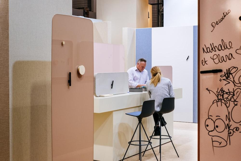 man and woman talking inside room with open door