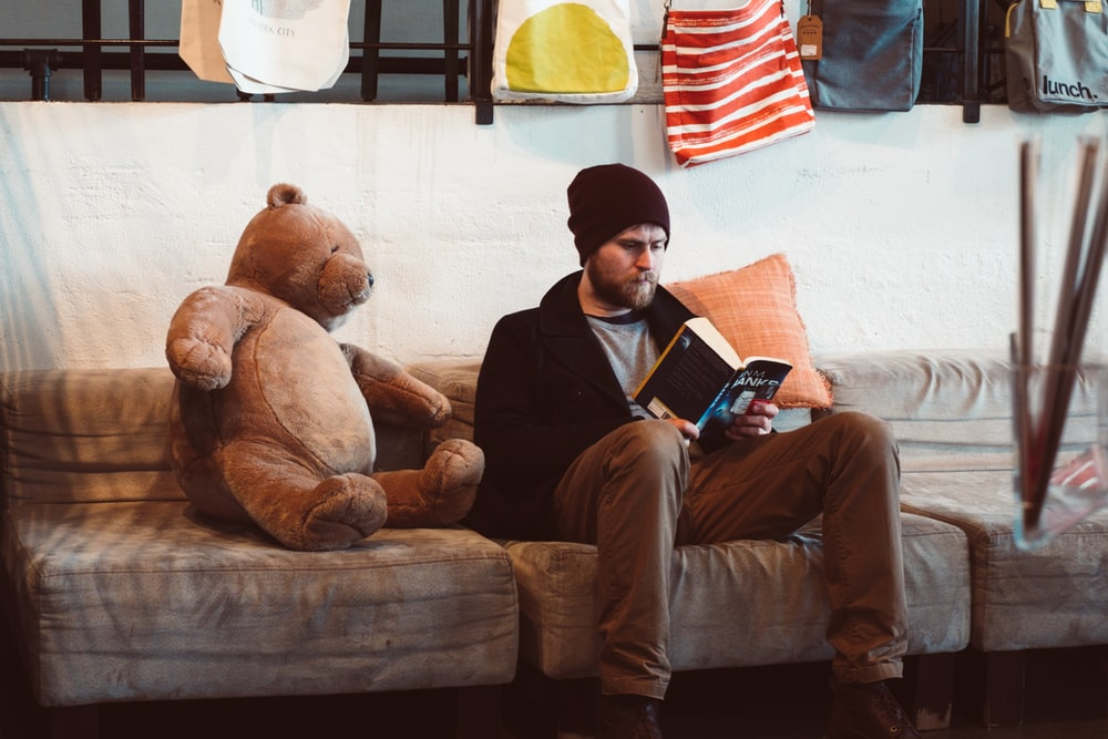 man sitting on sofa reading book near brown bear plush toy