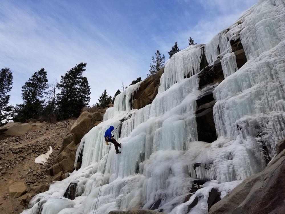 man rappelling down waterfalls