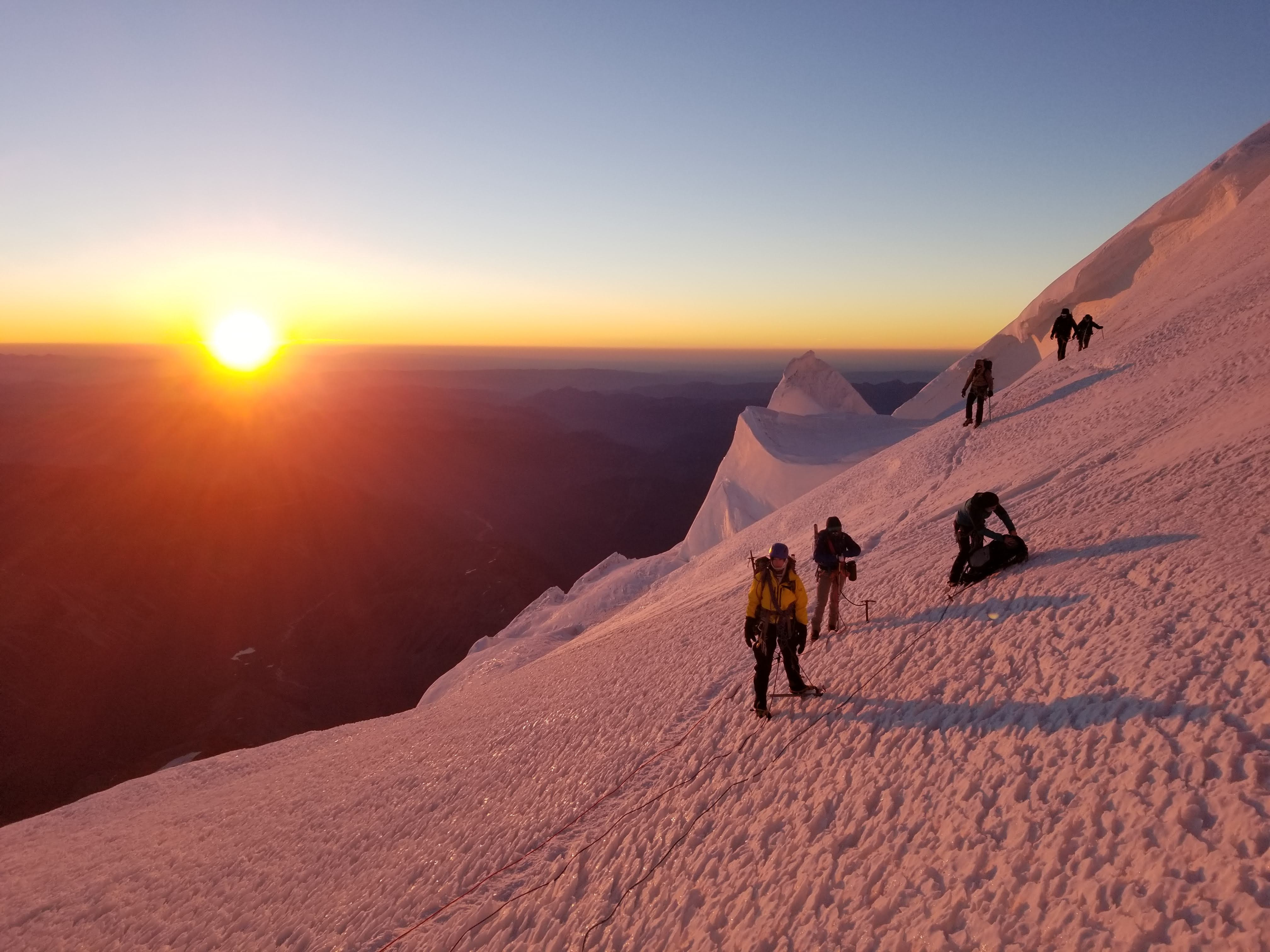 people on glacier mountain during sunset
