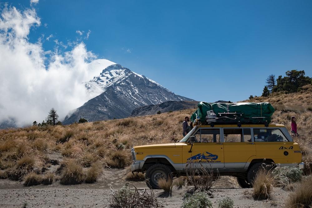 yellow SUV on road near mountain