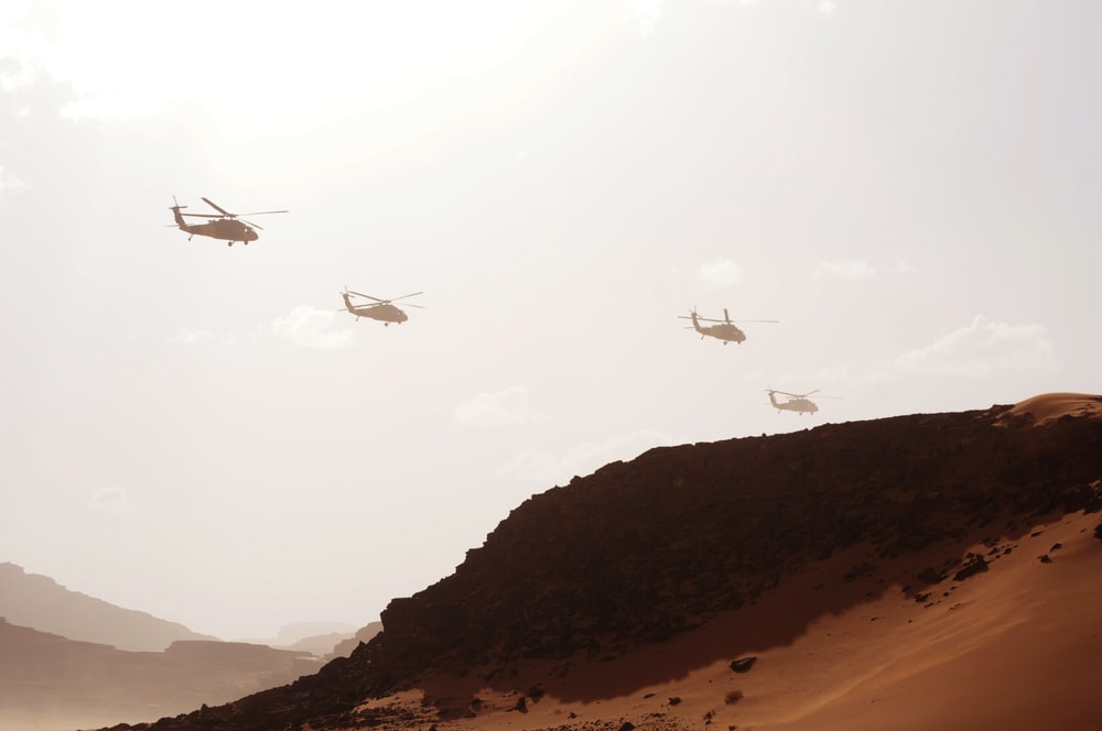 four helicopters over mountain at daytime