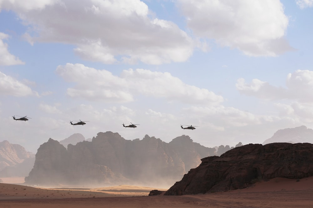 four helicopters in flight