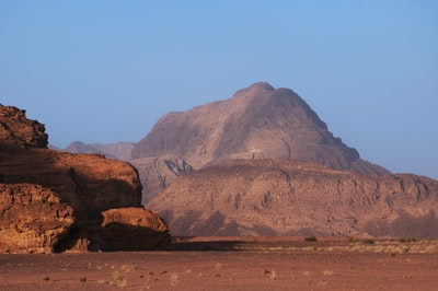 brown rock formation under blue sky during daytime jordan zoom background