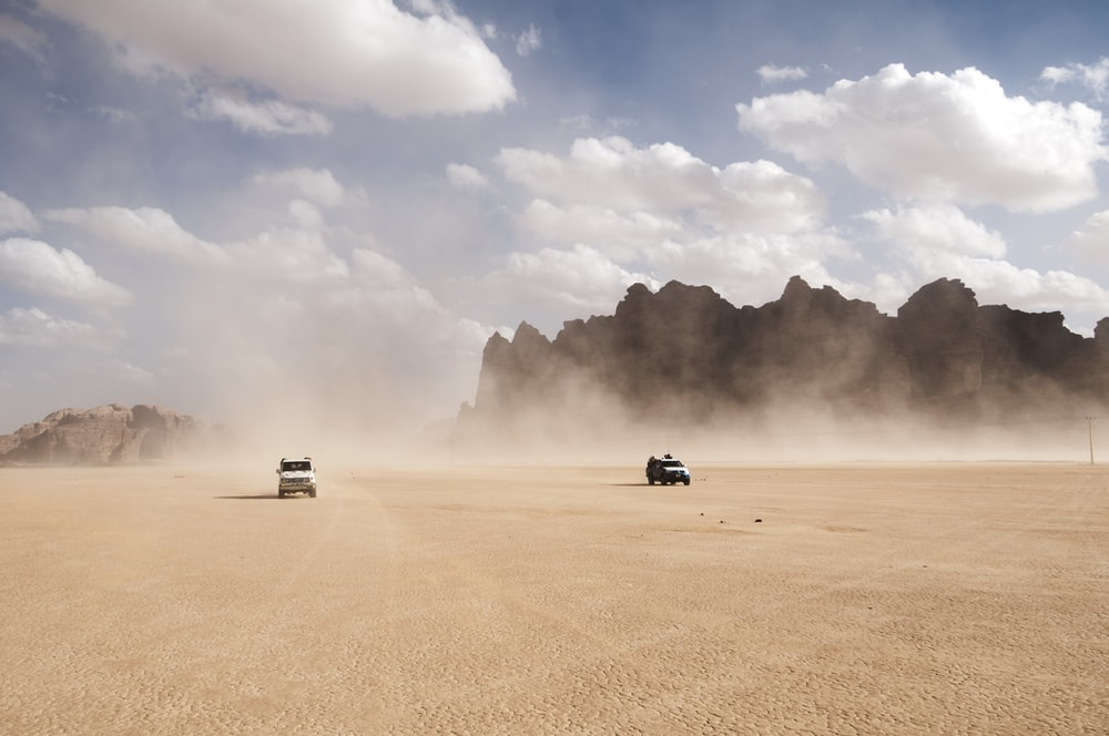 2 cars racing on dusty desert