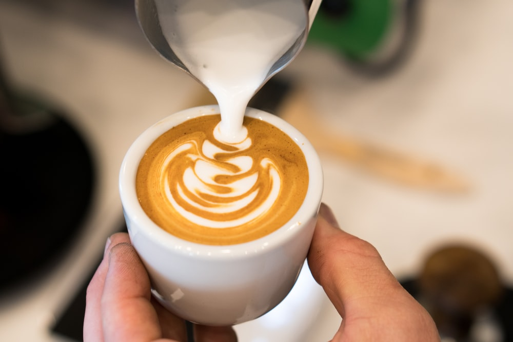 milk being poured on cappuccino