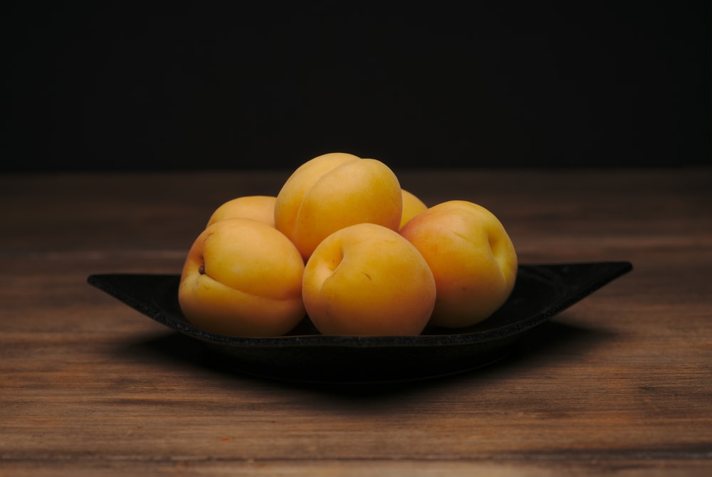 round yellow fruits on black plate