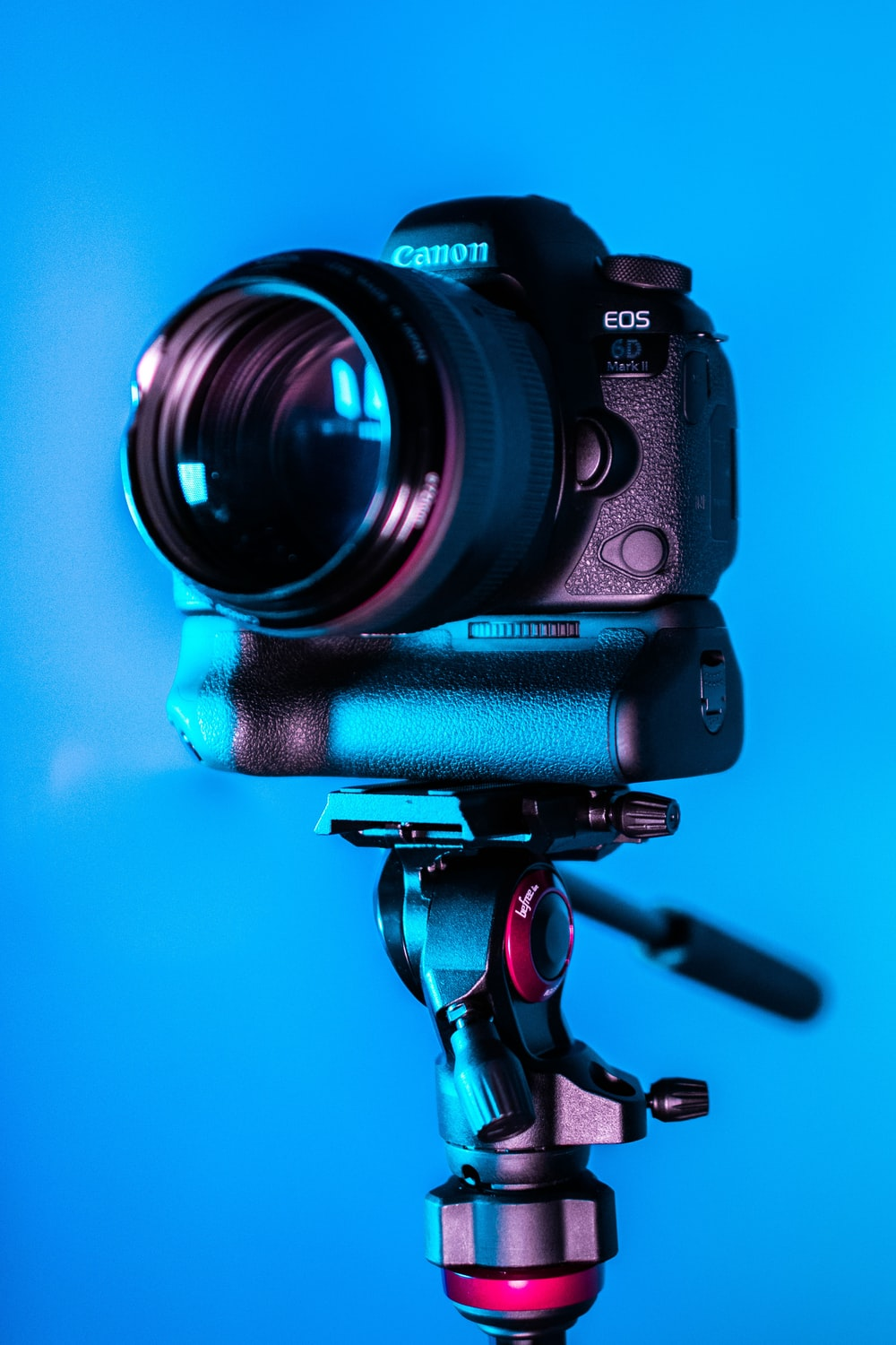 black Canon EOS DSLR camera with stand