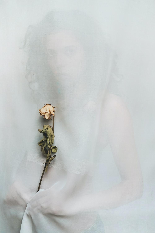 woman holding orange petaled flower
