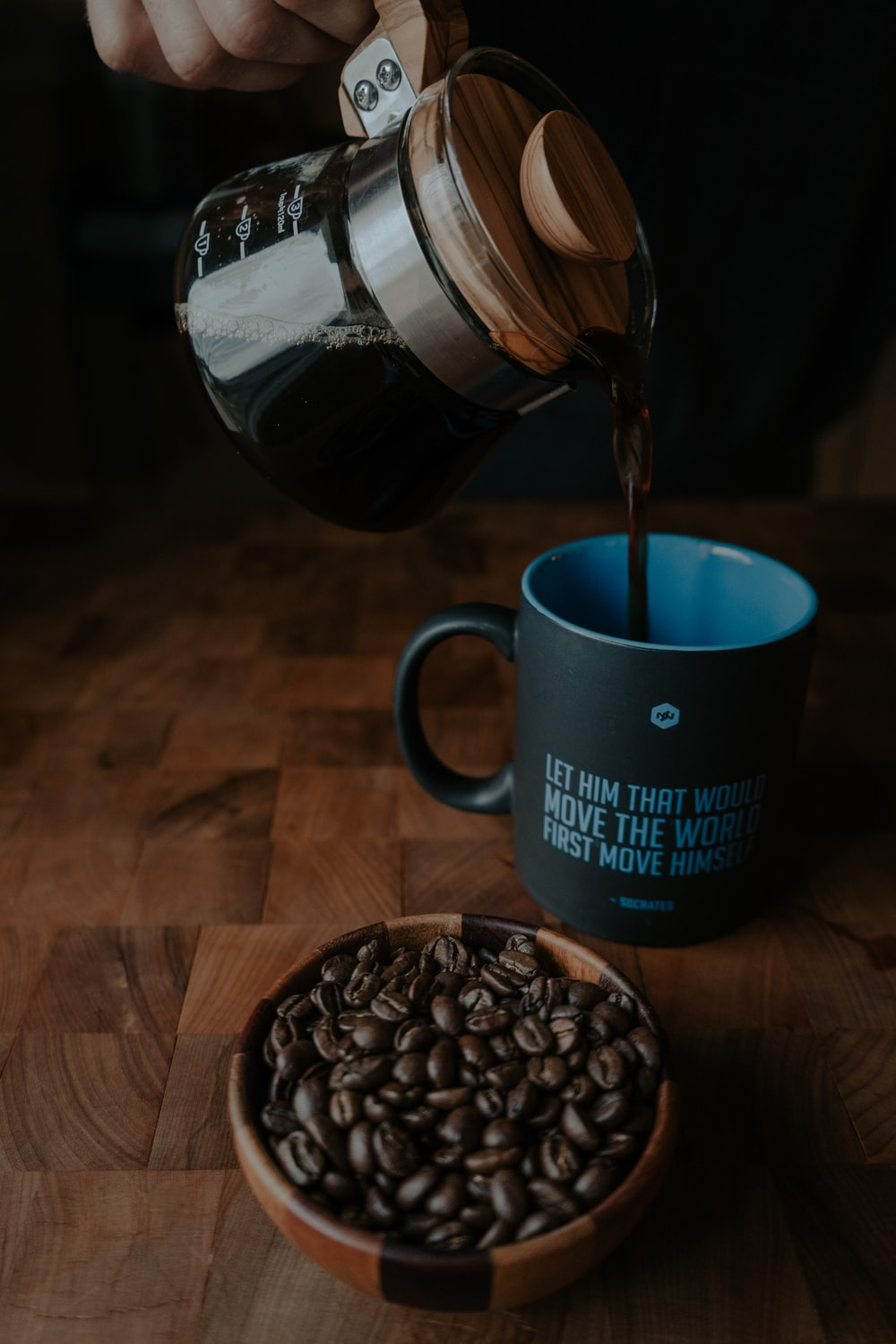 person pouring coffee on black mug beside coffee beans