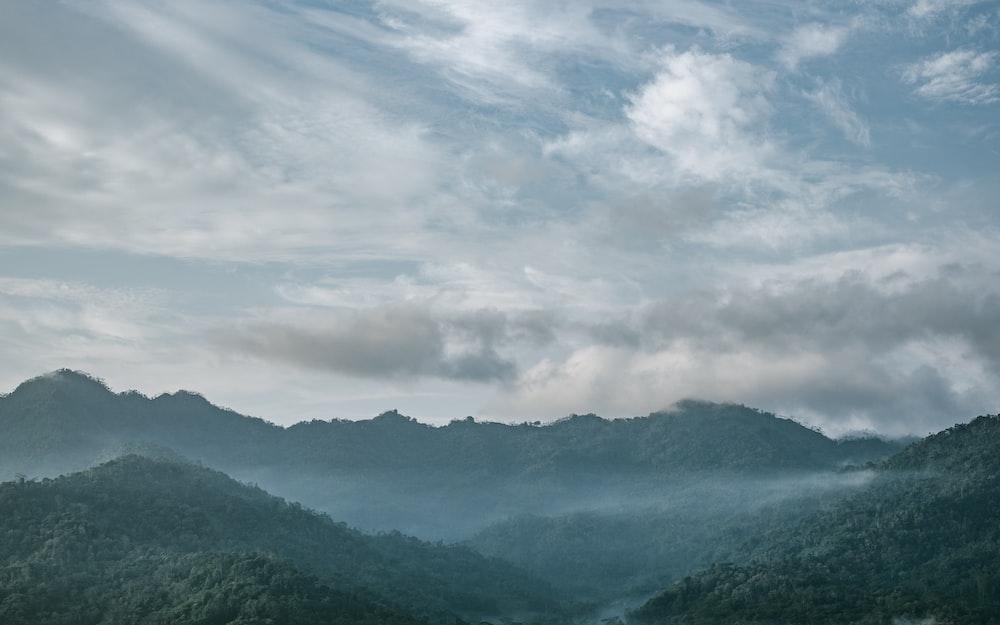 silhouette mountains under white sky
