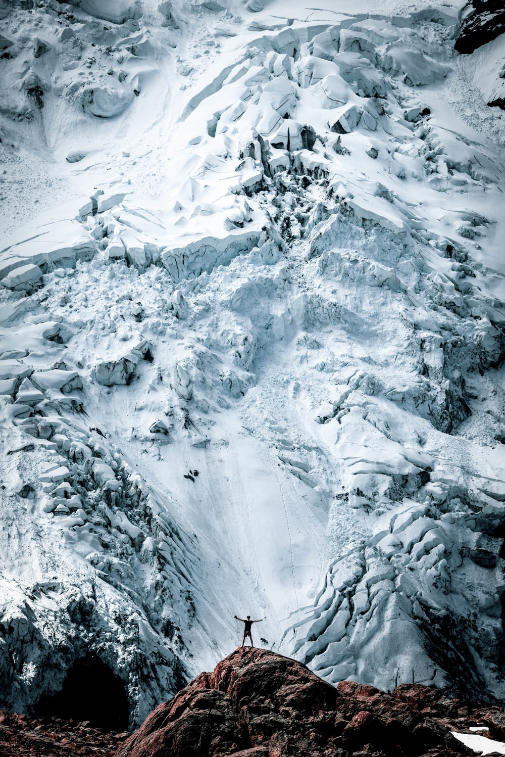 person standing on rock front of snow-capped mountain in nature photography