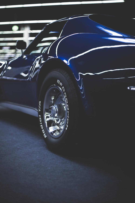 blue coupe on gray concrete pavement
