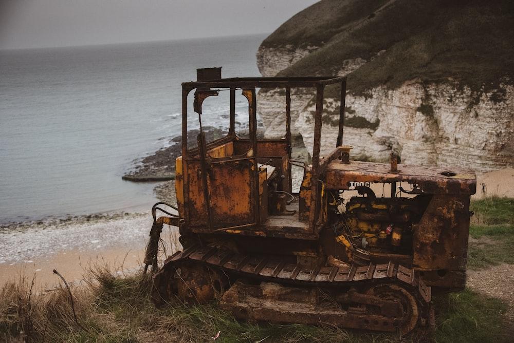 yellow bulldozer truck near seashore