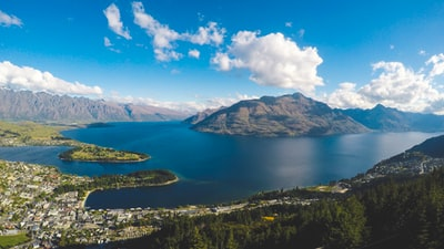 buildings near body of water and mountains under clear blue sky and white clouds at daytime new zealand zoom background