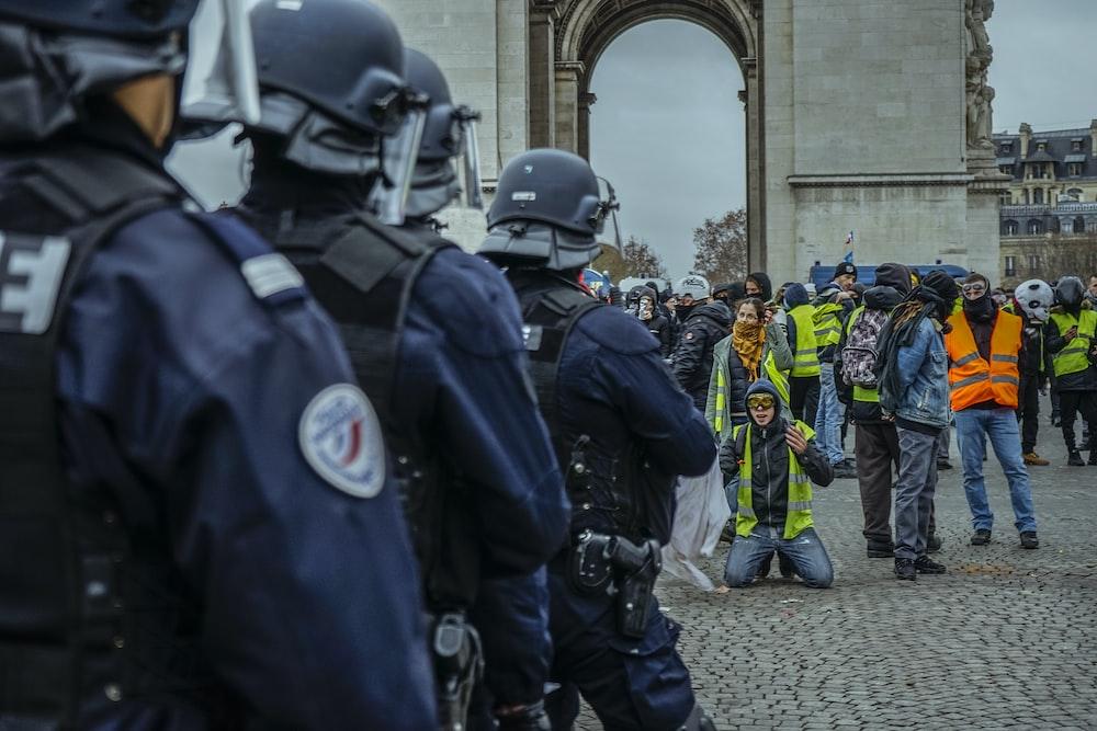 man kneeling in front of police