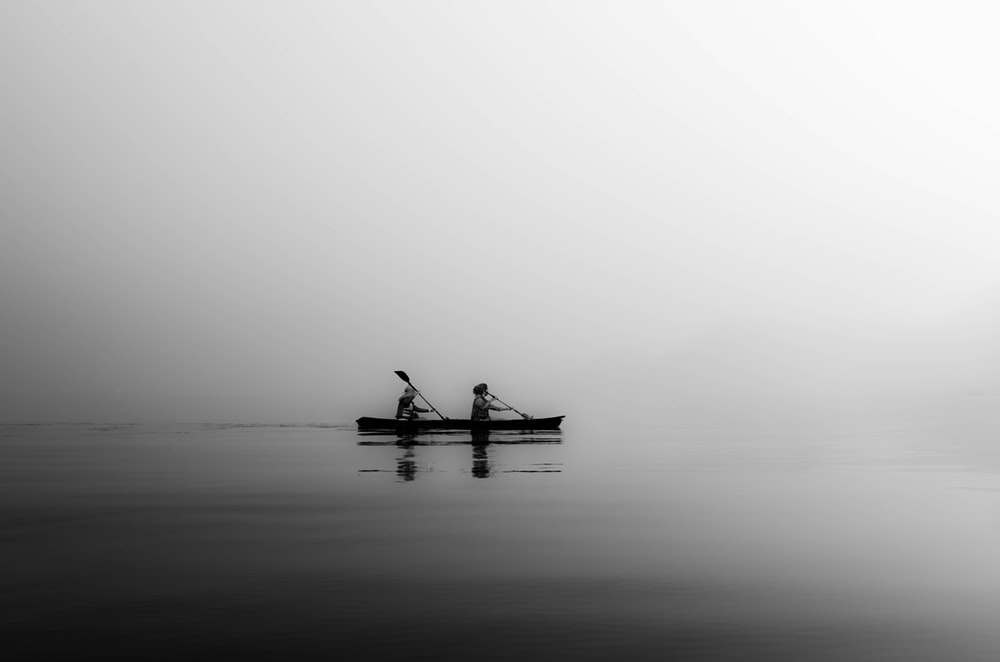 two person sailing on calm body of water