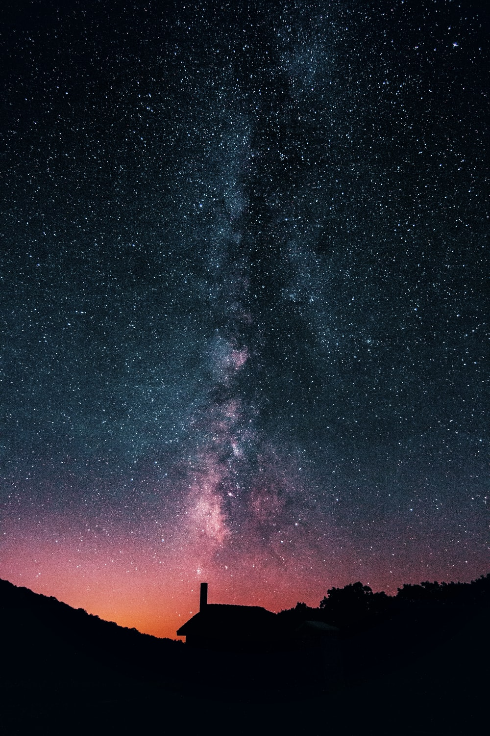 silhouette of house under starry night