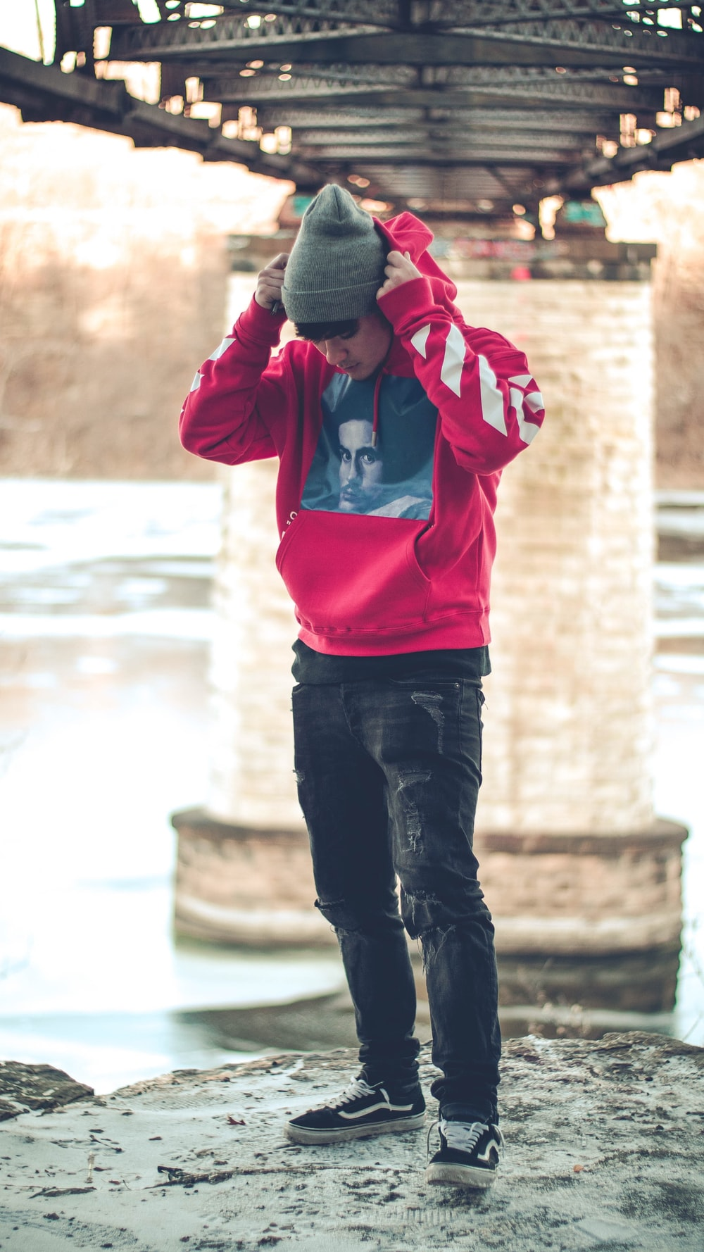 man in red pullover hoodie standing below the bridge